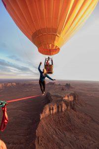 balancing on slackline between two hot air balloons